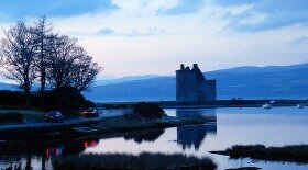 Lochranza Castle in dusk, with the Kintyre hills in the background